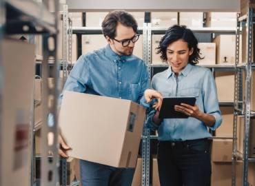 Deux individus dans un entrepôt, regardant une tablette portable, illustrant le module gestion commerciale d'un ERP