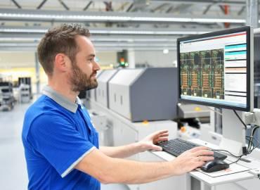 Homme devant un ordinateur dans une usine, illustrant le module gestion de production d'un ERP