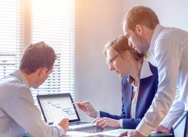Trois individus dans un bureau face à un ordinateur illustrant le module décisionnel d'un ERP