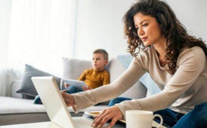 Femme travaillant sur ordinateur portable depuis son domicile, avec un enfant sur son canapé