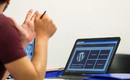 Homme travaillant sur ordinateur avec comme image le logo WordPress
