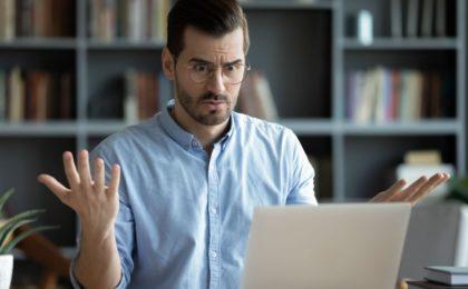 Homme énervé devant un ordinateur